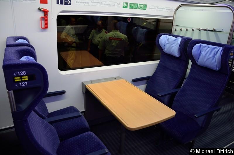 An diesem Tischplätzen sitzen zwei Personen neben einer Wand. Hinter den Sitzen gegenüber ist eine der vier Gepäckablagen des Zuges.